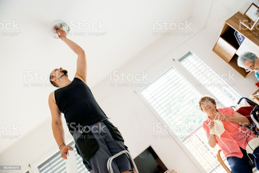 Maintainer In The Nursery Home Changing Light Bulb stock photo