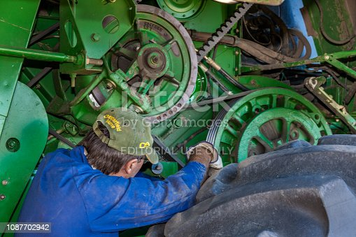 Moree, Australia - November 25, 2010: A farmer performs a maintenance routine on his John Deere combine harvester in Moree a major agricultural area in New South Wales, Australia.