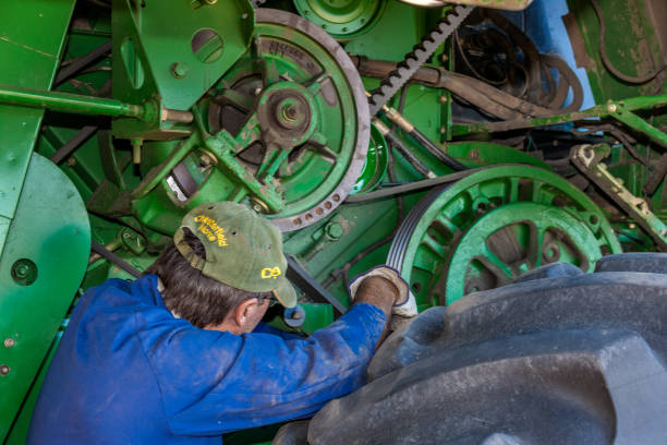Maintaining a combine harvester in Moree, Australia. Moree, Australia - November 25, 2010: A farmer performs a maintenance routine on his John Deere combine harvester in Moree a major agricultural area in New South Wales, Australia. agricultural equipment stock pictures, royalty-free photos & images