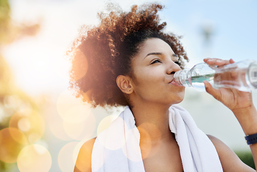 Cropped shot of a young woman enjoying a bottle of water while out for a run