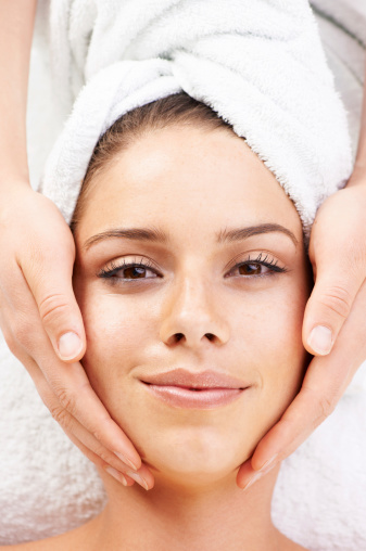 Gorgeous young woman with a towel around her head receiving a beauty treatment - portrait