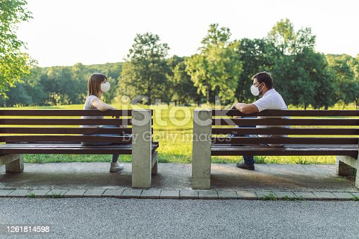 Two friends, a man and a woman are maintain a social distance by sitting on two separate benches in public park at a safe distance and wearing protective face masks during corona virus pandemic.