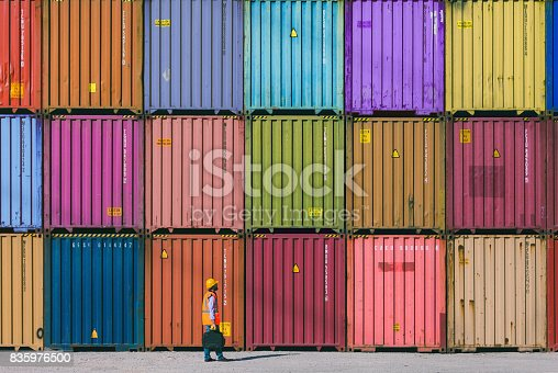 Engineer man with yellow crash helmet and worker west checking cargo freights in front of colorful cargo container stacks in shipping port
