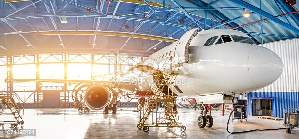 istock Maintenance and repair of aircraft in the aviation hangar of the airport, view of a wide panorama. 1074190274