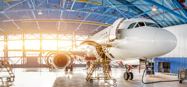 Maintenance and repair of aircraft in the aviation hangar of the airport, view of a wide panorama. stock photo