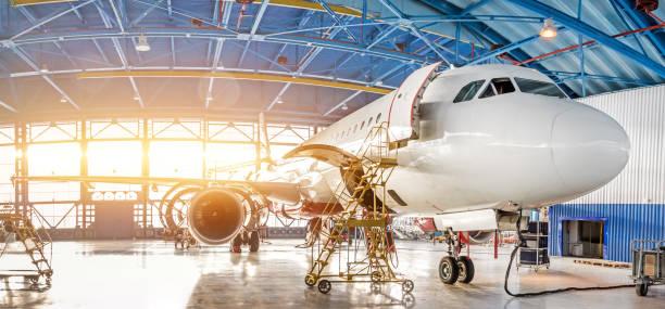 onderhoud en reparatie van vliegtuigen in de loods van de luchtvaart van de luchthaven, uitzicht op een breed panorama. - luchtvaartindustrie stockfoto's en -beelden