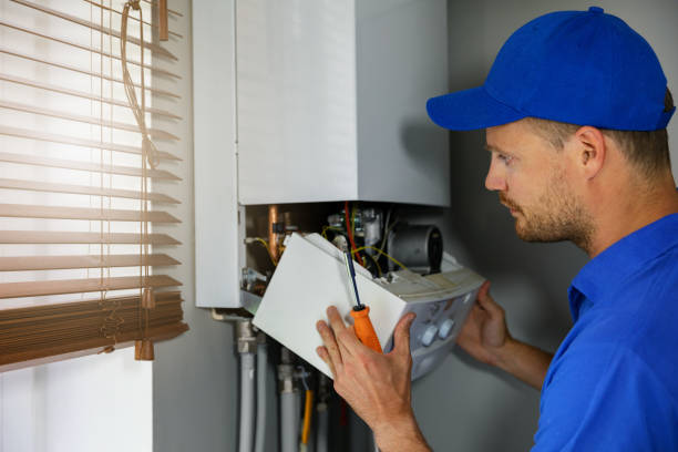 maintenance and repair service engineer working with house gas heating boiler stock photo