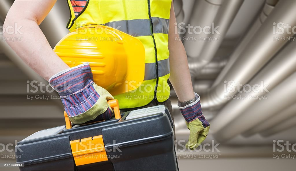 Maintenance concept. Technician and pipes in background. stock photo