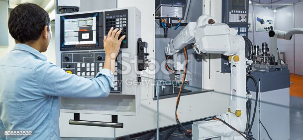istock Maintenance engineer controlling industrial robotic holding automotive part with CNC machine in smart factory 4.0 concept 808553532