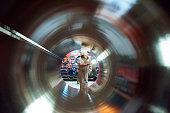 Busy female factory technician in hardhat focusing on work while examining tube at factory, view through object