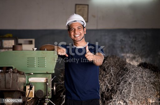 1047558948istockphoto Maintenance engineer giving thumbs up gesture at factory 1180995268