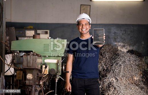 1047558948istockphoto Maintenance engineer holding digital tablet in industrial workshop 1180995435