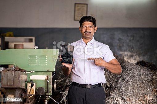 1047558948istockphoto Maintenance engineer pointing holding digital tablet in industrial workshop 1180995303