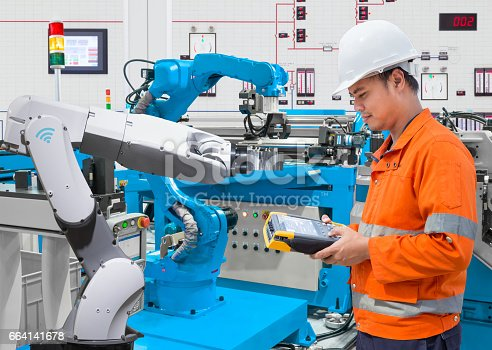 istock Maintenance engineer programing automated robotic at industry 4.0 concept 664141678