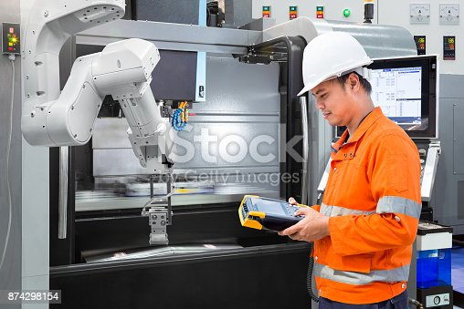 874298574 istock photo Maintenance engineer programming automatic robotic hand with CNC machine in smart factory. Industry 4.0 concept 874298154