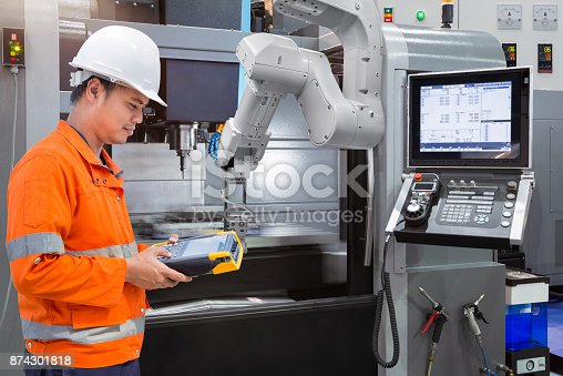 874298574 istock photo Maintenance engineer programming automatic robotic hand with CNC machine in smart factory. Industry 4.0 concept 874301818