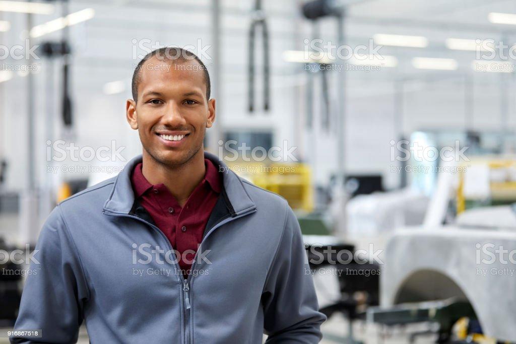 Instandhalter lächelnd in Autohaus – Foto