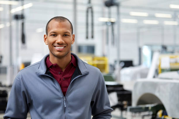 Maintenance engineer smiling in car showroom stock photo