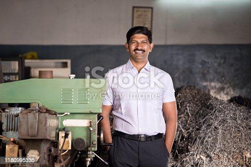 1047558948istockphoto Maintenance engineer standing with machine at factory 1180995335