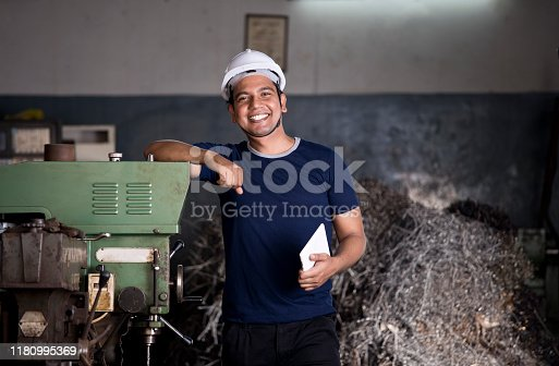 1047558948istockphoto Maintenance engineer standing with machine at factory 1180995369