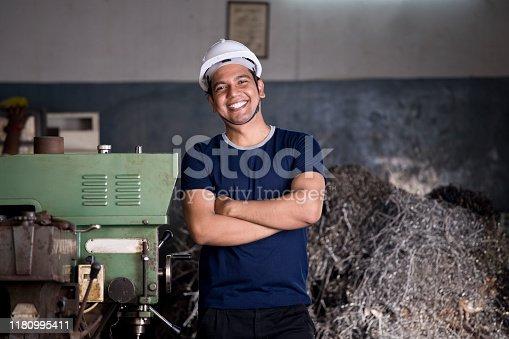 1047558948istockphoto Maintenance engineer standing with machine at factory 1180995411