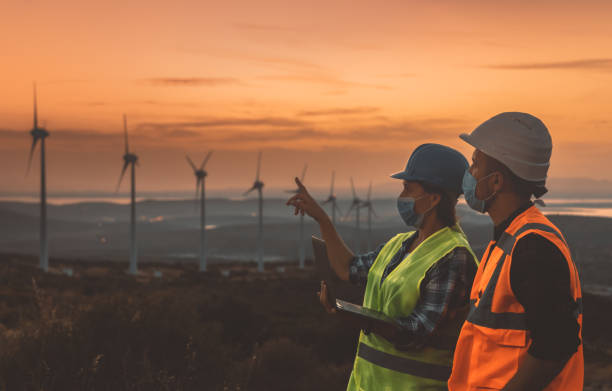 Maintenance engineer team with face mask working in wind turbine farm at sunset during pancemic stock photo