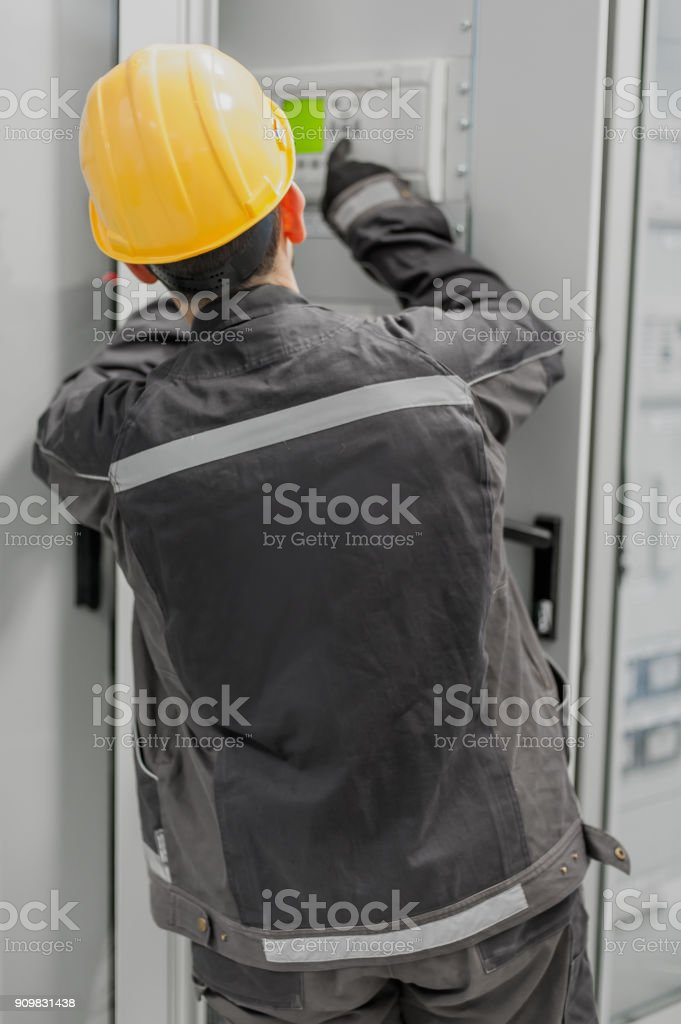 Maintenance engineer testing voltage switchgear and bay control unit stock photo