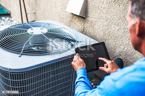 istock Maintenance engineer using digital tablet to inspect air conditioning unit 612818866