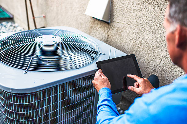 Maintenance engineer using digital tablet to inspect air conditioning unit stock photo