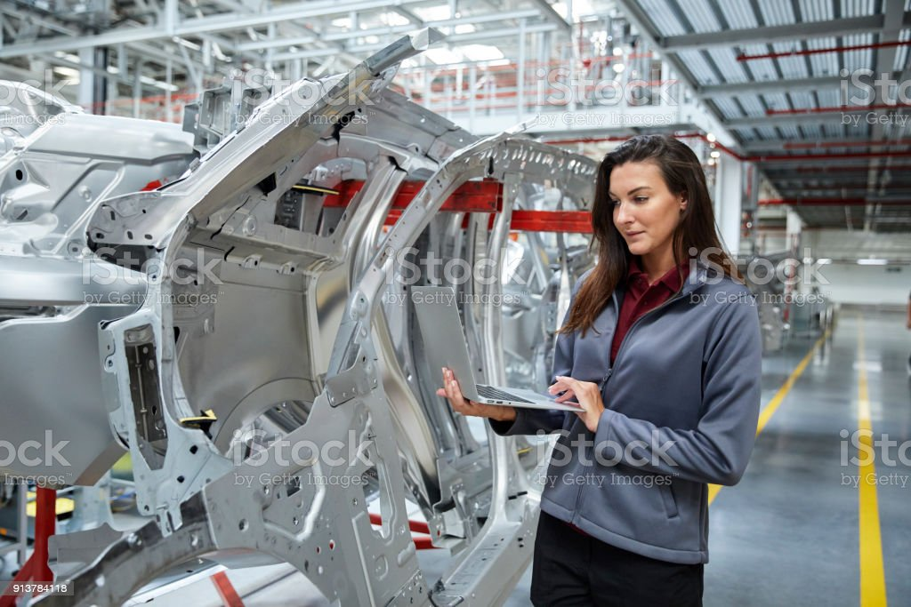Maintenance engineer using laptop by car chassis stock photo