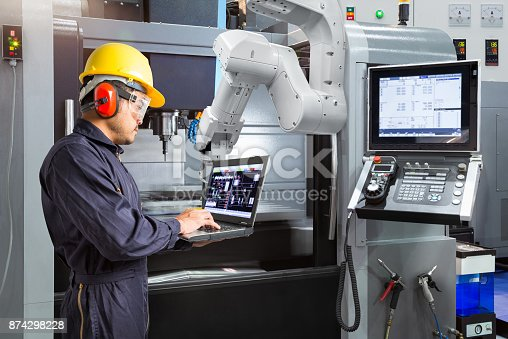 874298574 istock photo Maintenance engineer using laptop computer control automatic robotic hand with CNC machine in smart factory. Industry 4.0 concept 874298228