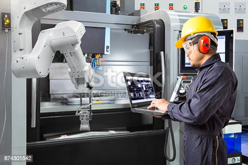 874298574 istock photo Maintenance engineer using laptop computer control automatic robotic hand with CNC machine in smart factory. Industry 4.0 concept 874301542