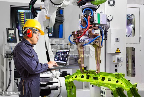 istock Maintenance engineer using laptop computer control robot grip automotive workpiece in smart factory, Industry 4.0 concept 1130500789