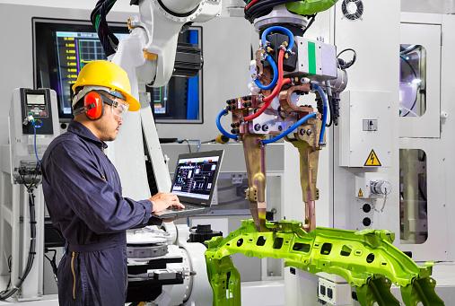 istock Maintenance engineer using laptop computer control robot grip automotive workpiece in smart factory, Industry 4.0 concept 1130500789