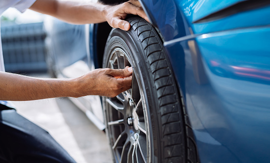 Maintenance male checking and removing tire valve filling nitrogen service on street at gas station, Safety vehicle to reduce accidents before a long travel, Blue car of man transportation lifestyle