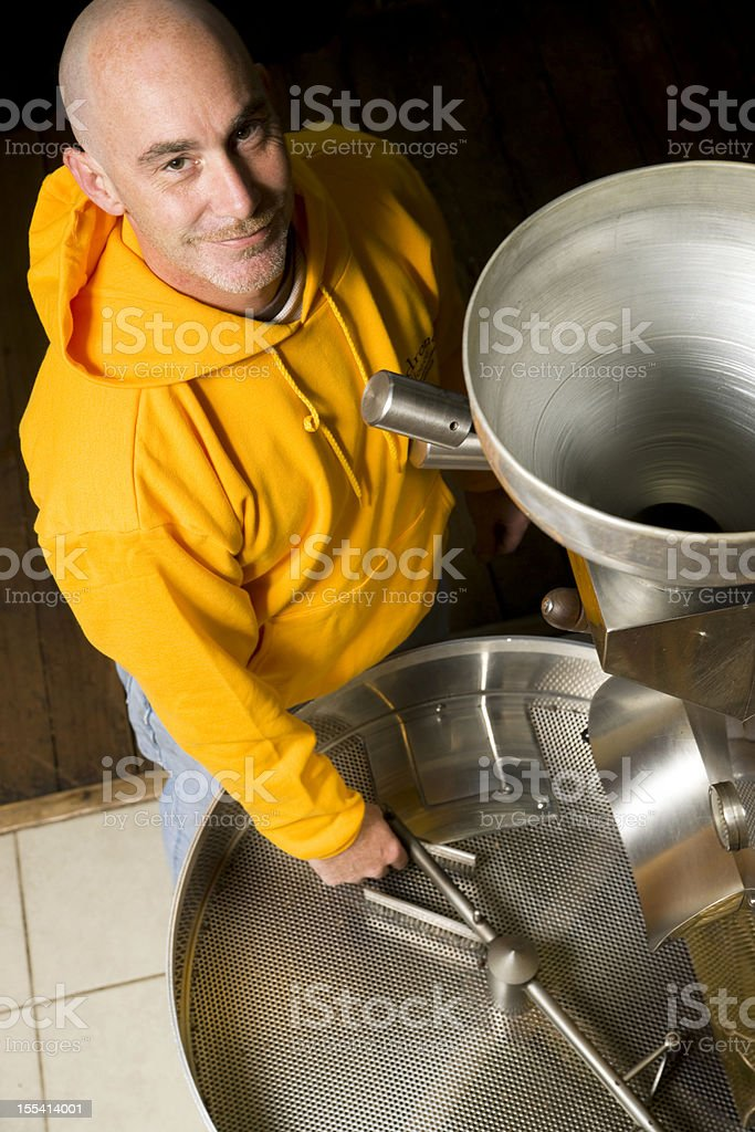 Maintenance Man Tending Equipment in Commericial Coffee Roaster stock photo