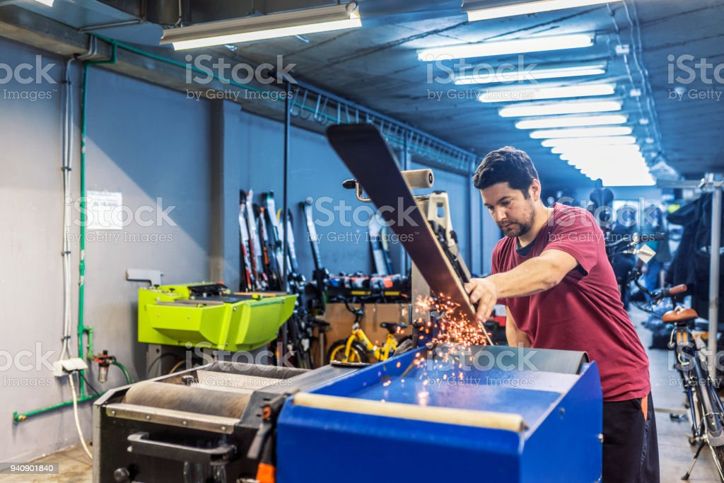 Maintenance of skis. Grinding and sparks. Ski service stock photo