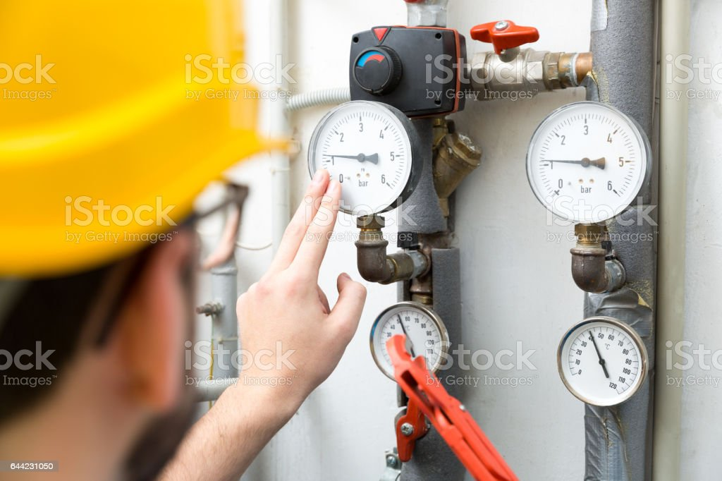 maintenance - technician checking pressure meters for house heating system stock photo