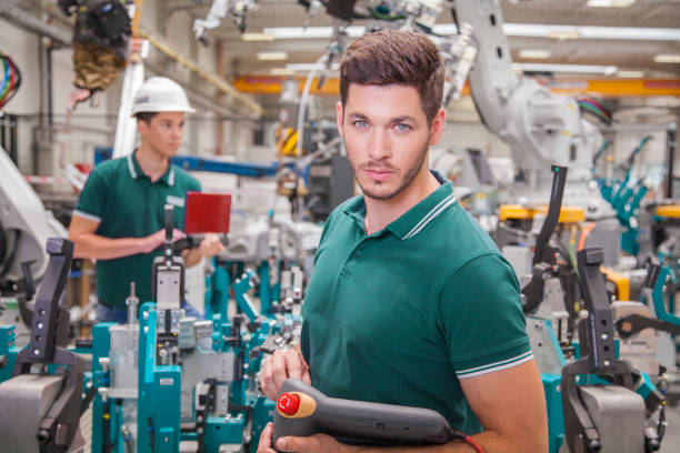 maintenance technicians team while programming robots technician team while robot maintenance in a welding shop of a car manufacture mechanical engineering stock pictures, royalty-free photos & images
