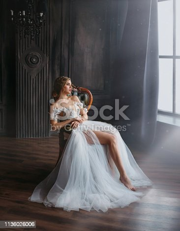 majestic and proud princess girl in white chic oriental white silver dress tired sitting on chair, lady shows off her slender leg and waiting for prince, gentle stylish image of graduate 2019.