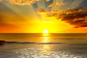 Majestic bright sunrise over ocean and light waves on blue sea.