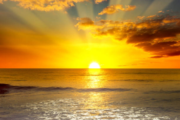 Majestic bright sunrise over ocean Majestic bright sunrise over ocean and light waves on blue sea. sunrise stock pictures, royalty-free photos & images