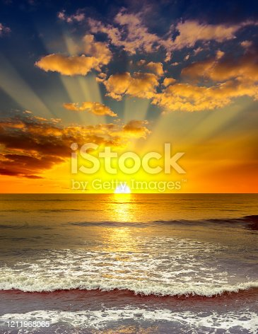 Majestic bright sunrise over the ocean. Calm sea and orange clouds.