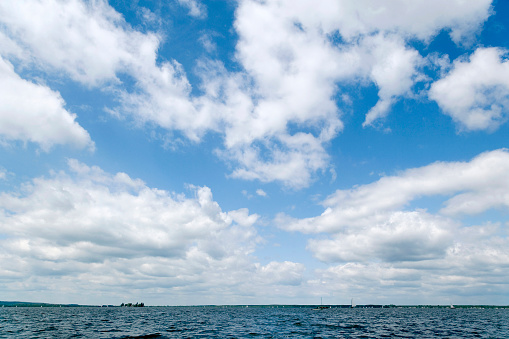 Majestic white clouds and blue sky lakeside. Exposure with extreme wide-angle lens. Useful for backgrounds.