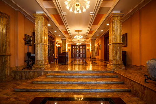 Luxurious lobby with steps, surrounded by row of marble pillars.