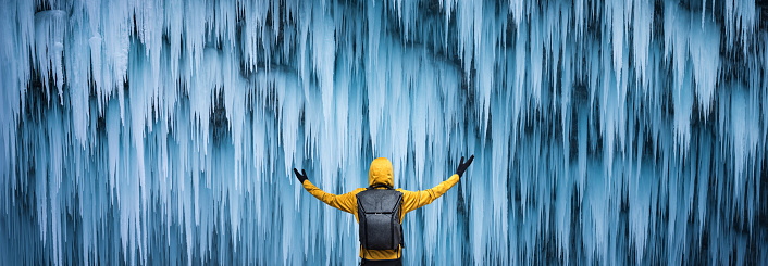 Man in yellow jacket watching a spectacular frozen waterfall (Pericnik, Slovenia).