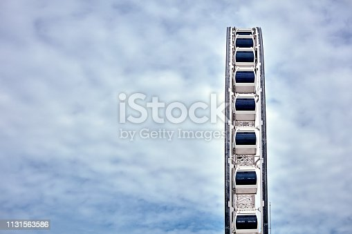 Majestic grand Ferris wheel on the background of clouds and blue sky. Low angle view.