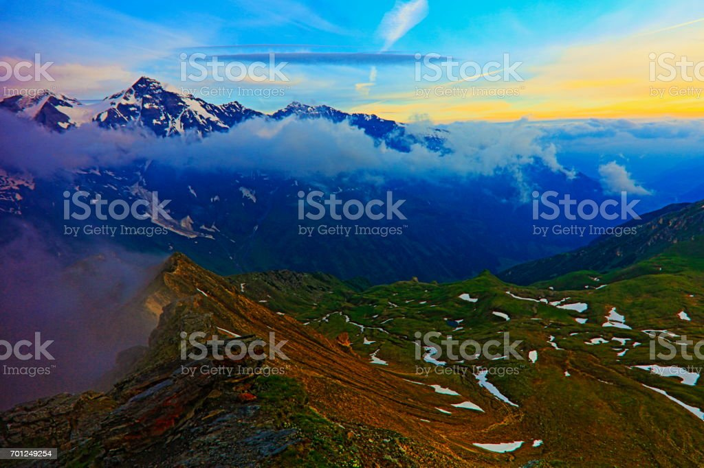 majestic Hohe Tauern snowcapped Austrian mountain range at sunrise - Tirol Alps dramatic cloudscape Sky and landscape and Grossglockner Massif stock photo