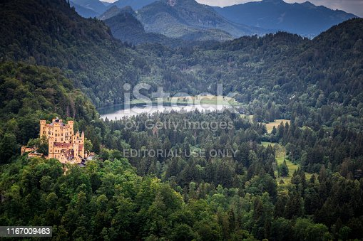Schwangau, Germany - 3 August, 2019: exterior view of the architecture of Neuschwanstein Castle near the village of Schwangau in Bavaria, southern Germany. The palace was commissioned by Ludwig II of Bavaria as a retreat and in honour of Richard Wagner. Ludwig paid for the palace out of his personal fortune and by means of extensive borrowing, rather than Bavarian public funds. The castle was intended as a home for the king, until he died in 1886. It was open to the public shortly after his death. Since then more than 61 million people have visited Neuschwanstein Castle. More than 1.3 million people visit annually, with as many as 6,000 per day in the summer.