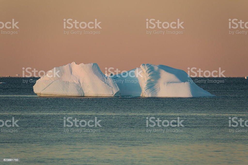 Majestic iceberg with orange sky stock photo
